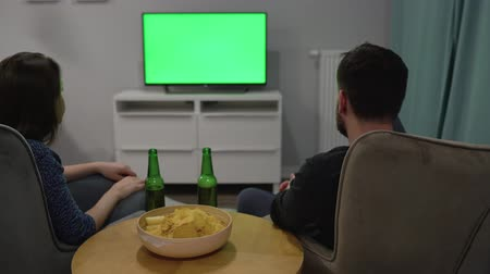 beer house : Man and woman are sitting in chairs, watching TV with a green screen, drink beer, eat chips and discuss what they see. Back view. Chroma key. Timelapse