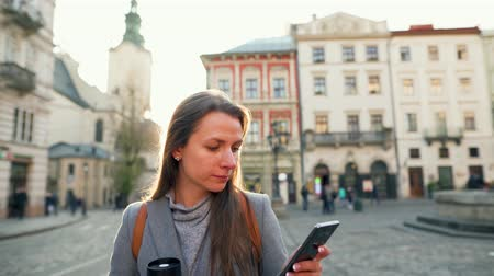 kolf : Young woman with a flask cup in hand walking down an old street using smartphone at sunset. Communication, social networks, online shopping concept. Stockvideo