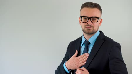 удовлетворенный : Portrait of a formally dressed bearded man with glasses straightens his tie and looks at the camera