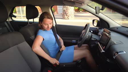auto parking : Woman in blue dress fastening car safety seat belt while sitting inside of vehicle before driving