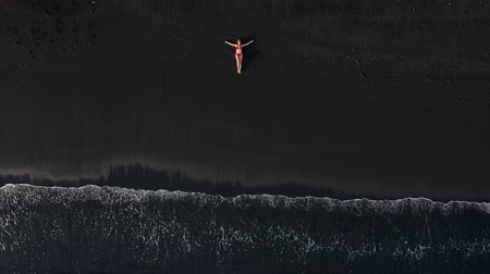 hazugság : Top view of a woman in a red swimsuit lying on a black beach on the surf line. Coast of the island of Tenerife, Canary Islands, Spain.