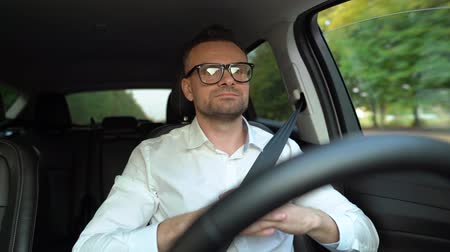 função : Bearded man in glasses and white shirt driving a car in sunny weather and uses autopilot function while driving