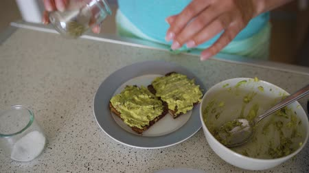 smashing : Woman cooking avocado toast, sprinkles it with salt and spices