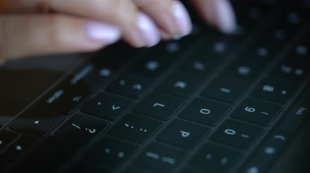 inputting : Close-up of female hands use a laptop for typing late at night
