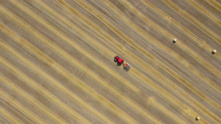 bales : Aerial view of haymaking processed into round bales. Red tractor works in the field. Shot at different speeds - normal and accelerated