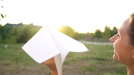 aeroespaço : Woman launches paper airplane against sunset background. Dreaming of traveling or the profession of a stewardess. Shot at different speeds - normal and slow motion