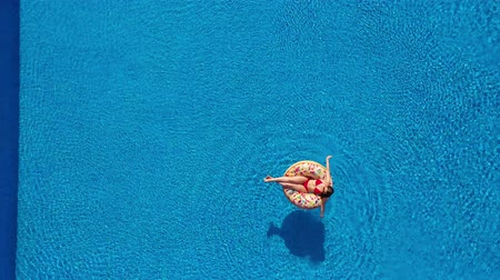 rosquinhas : Aerial view of a woman in red bikini lying on a donut in the pool Stock Footage