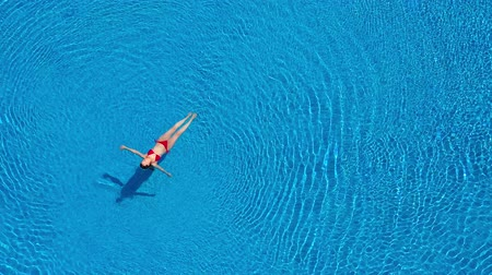 bugia : View from the top as a woman in a red swimsuit swimming and lying on her back in the pool. Relaxing concept