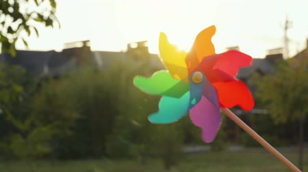 ventilátor : Plastic rainbow windmill rotates on the background of blurry houses and sunset. Suburbs Concept Dostupné videozáznamy