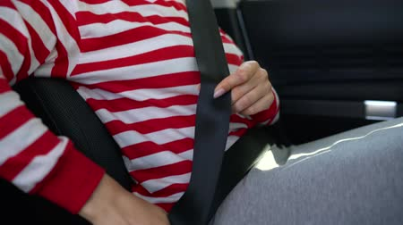 auto parking : Woman fastening car safety seat belt while sitting inside of vehicle before driving