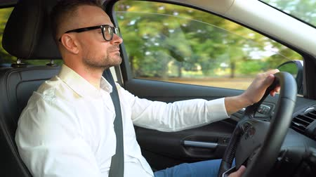 automovilismo : Bearded man in glasses and white shirt driving a car in sunny weather