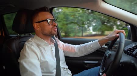 motoring : Bearded man in glasses and white shirt driving a car in sunny weather and swears at others behind the scenes Stock Footage