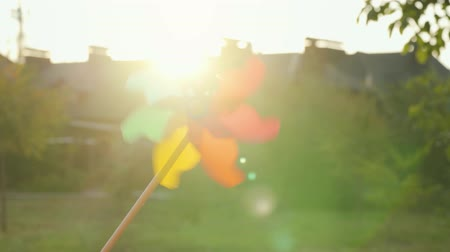 propeller toy : Plastic rainbow windmill rotates on the background of blurry houses and sunset. Suburbs Concept Stock Footage