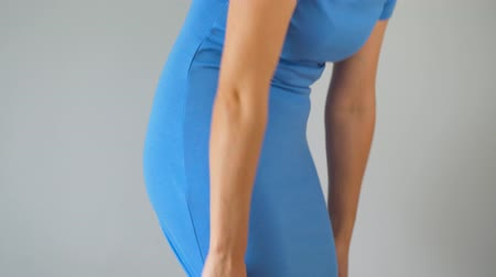 onderbroek : Woman in slimming panties wears a blue dress on top and checks the result. Concept of aspiration for a perfect body