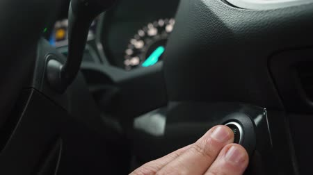 стартер : Male hand pushes engine start stop button in a modern car interior