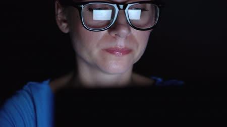 nagyító : Woman in glasses working behind a laptop at night. Monitor screen is reflected in the glasses