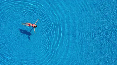 mentira : View from the top as a woman in a red swimsuit lying on her back in the pool. Relaxing concept