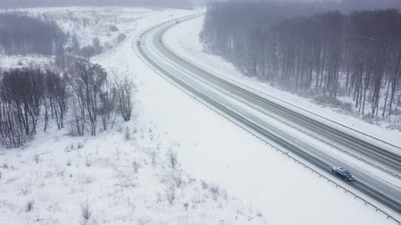 vagão : Aerial view of traffic on a road surrounded by winter forest in snowfall Vídeos