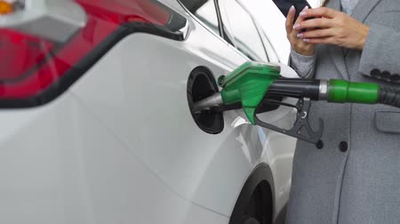 tankowanie : Woman using smartphone while her car is refueling. Slow motion