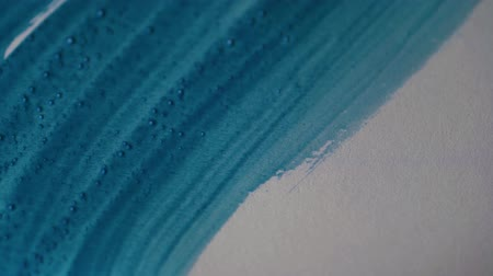 グワッシュ水彩画 : Drawing with a paintbrush on white paper with blue watercolor close up. Texture and background 動画素材
