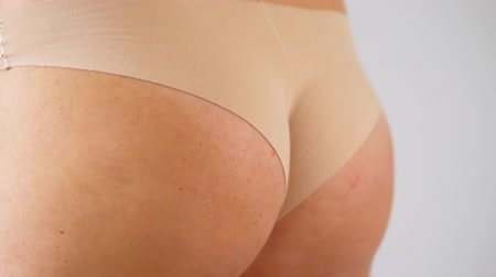 onderbroek : Woman squeezes buttocks. Cellulite of the first degree appears on the skin