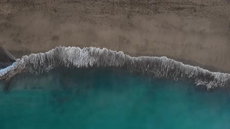 alcanzando : Top view of the desert black beach on the Atlantic Ocean. Coast of the island of Tenerife. Aerial drone footage of sea waves reaching shore