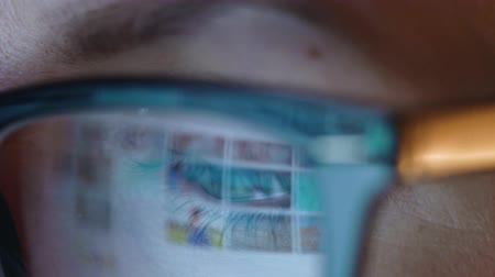 tükrözött : Woman in glasses looking on the monitor and surfing Internet. The monitor screen is reflected in the glasses. Extreme close up