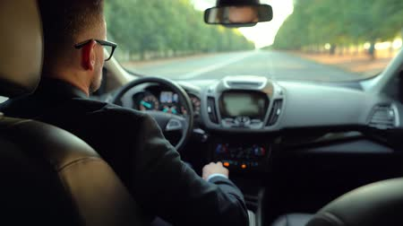 motoring : Formally dressed bearded man in glasses driving a car in sunny weather. View from the back seat of a car Stock Footage