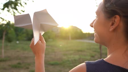 odstín : Woman launches paper airplane against sunset background. Dreaming of traveling or the profession of a stewardess. Slow motion Dostupné videozáznamy