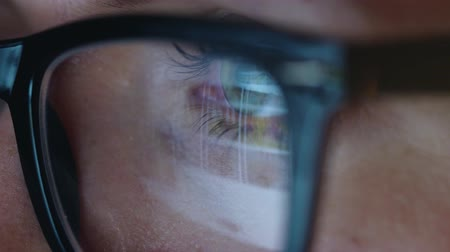 looking distance : Woman in glasses looking on the monitor and surfing Internet. The monitor screen is reflected in the glasses. Extreme close up