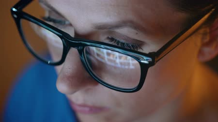nagyítóüveg : Woman in glasses looking on the monitor and surfing Internet. The monitor screen is reflected in the glasses Stock mozgókép