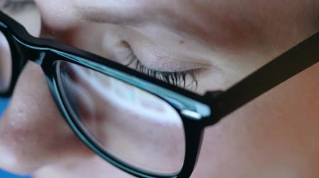 nagyító : Woman in glasses looking on the monitor and surfing Internet. The monitor screen is reflected in the glasses. Extreme close up