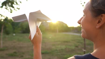rukojeť : Woman launches paper airplane against sunset background. Dreaming of traveling or the profession of a stewardess Dostupné videozáznamy