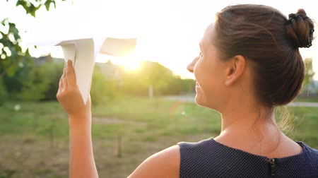 işlemek : Woman launches paper airplane against sunset background. Dreaming of traveling or the profession of a stewardess. Slow motion Stok Video