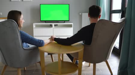 pocałunek : Man and woman are sitting in chairs, kissing and watching TV with a green screen, switching channels with a remote control. Back view. Chroma key. Indoors