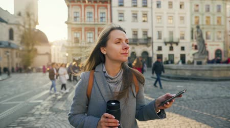 beuta : Woman with a flask cup in hand walking down an old street using smartphone at sunset. Communication, social networks, online shopping concept.