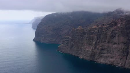rendes : Aerial view of Los Gigantes Cliffs on Tenerife overcast, Canary Islands, Spain. Shot at different speeds - normal and accelerated