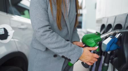 hořlavý : Woman fills petrol into her car at a gas station close-up Dostupné videozáznamy