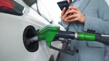 giderler : Woman using smartphone while her car is refueling. Slow motion
