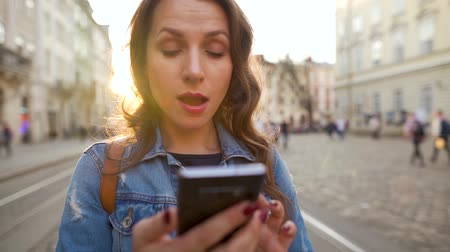 exited : Young woman walking down an old street using smartphone and is very happy that she sees there. Win or big luck concept. Slow motion