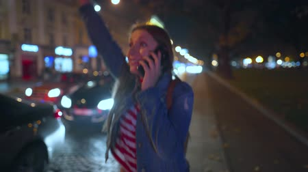 exited : Woman is very emotionally talking with her friend on a smartphone, sees him and waves him joyfully on the street of the evening city