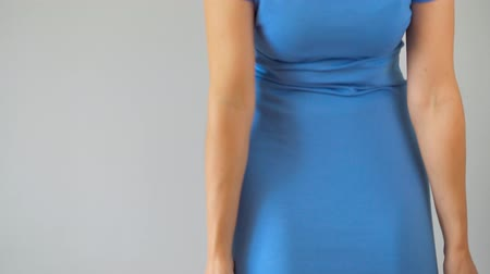 coxa : Woman in slimming panties wears a blue dress on top and checks the result. Concept of aspiration for a perfect body