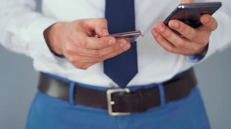 debit : Formally dressed man selects a credit card from several and enters it number into a smartphone to pay online. Online shopping, lifestyle technology. Close-up