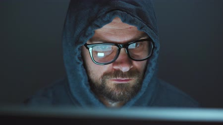 roubo : Male hacker in the hood and glasses working on a computer in a dark office room. Cybercrime concept