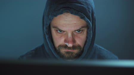 włamywacz : Male hacker in the hood working on a computer in a dark office room Wideo