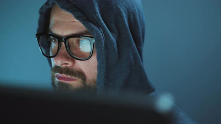 protege : Male hacker in the hood and glasses working on a computer in a dark office room. Cybercrime concept