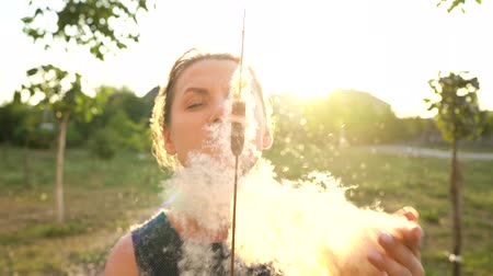 sentido : Woman blows on reeds outdoors in sunny day. Fluff from reeds flies around. Slow motion