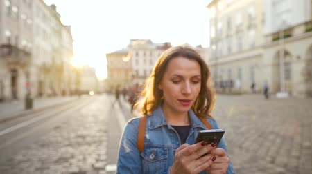 exited : Woman walking down an old street using smartphone and is very happy that she sees there. Win or big luck concept. Slow motion Stock Footage