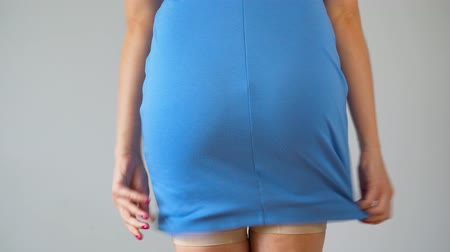liposukcja : Woman in slimming panties wears a blue dress on top and checks the result, back view. Concept of aspiration for a perfect body