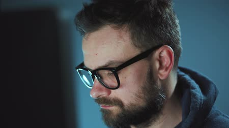 włamywacz : Bearded male hacker in hoodie and glasses working on a computer in a dark office room. Cybercrime concept